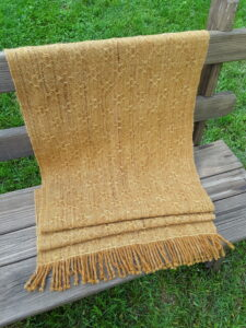 handwoven lace shawl on a bench