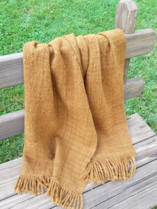 handwoven lace stole draped on a bench